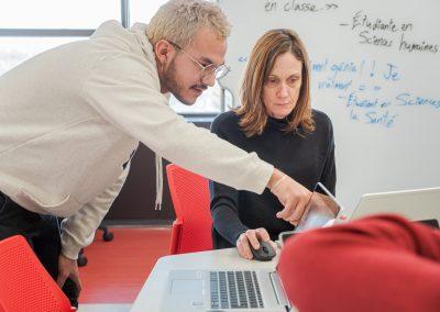 Un étudiant du programme d'intégration multimédia montre à une professeur le porte-clé 3D qu'il a conçu.