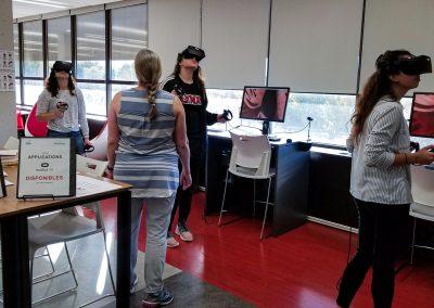 La professeur guide trois étudiantes qui observent l'intérieur du coeur à l'aide de la réalité virtuelle à partir d'un poste Oculus Rift avec l'application ShareCare.